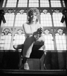 A black and white photo of David Bowie sat on a chair legs crossed staring down the lens of the camera
