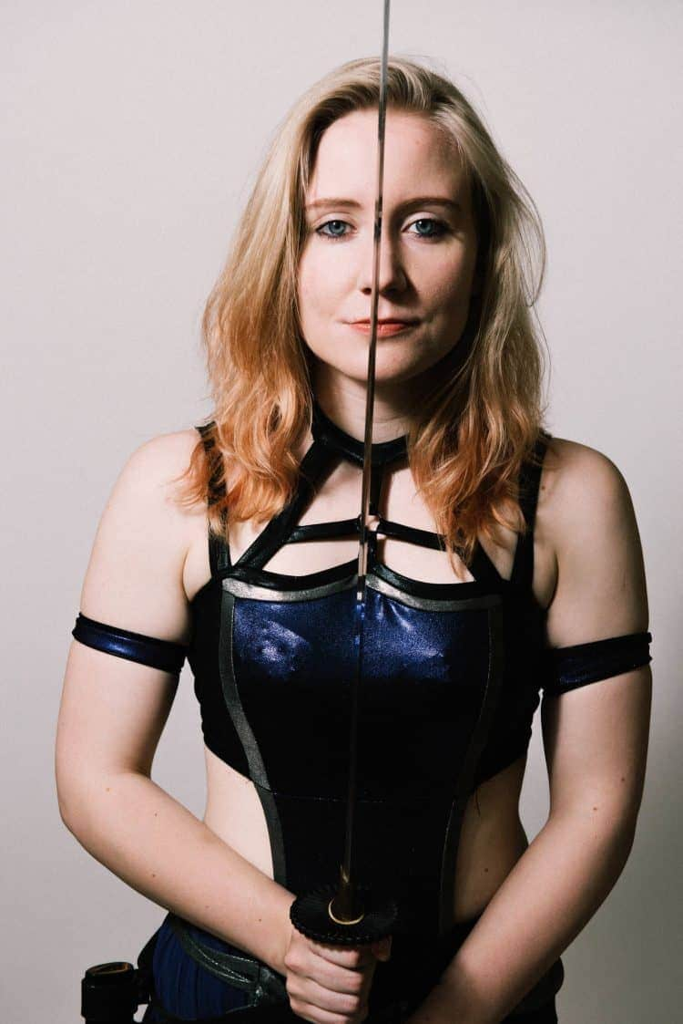 British Wrestler Pollyanna stands holding a sword betwwen her eyes as she stares into camera. She is wearing a costume reminiscent of a Game Of Thrones character
