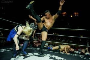Wrestler Pollyanna being axe kicked in the ring