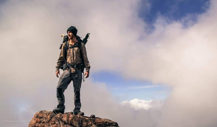 Adventurer Ash Dykes stands on top of a mountain in Madagascar. A chicken's head can be seen poking out of his rucksack. Pic taken by Suzanna Tierie