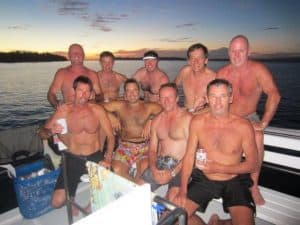 Brett Archibald on the back of a boat with his mates. All men have their tops off and shorts on