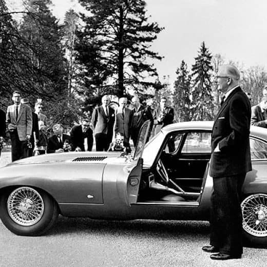 Creater of the E Type Jaguar Sir William Lyons stands by his creation with a crowd looking on