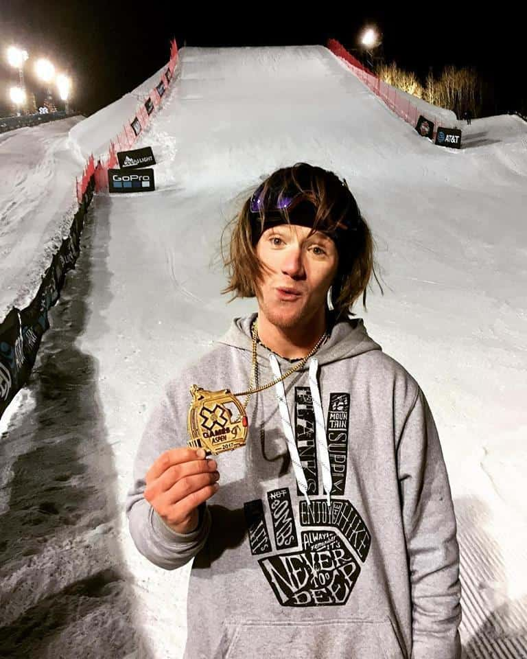 James 'Woodsy' Woods stands at the bottom of a slope holding his winning X Games medal in front of him
