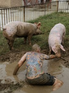 Tim Steiner from Zurich sits in mud with his back to camera stroking a pig for exhibition Art Farm in Yang Zhen