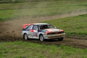 A white, red and black Audi Quattro raleigh car speeds through a mud track kicking up dirt as it goes