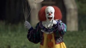 Tim Curry as Pennywise from the 1990 series IT. The clown laughhs and points a finger as he holds some white balloons