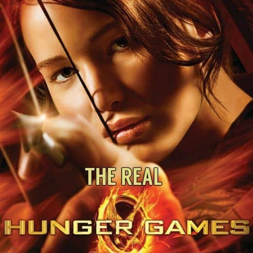 Jennifer Laurence on the poster for the first Hunger Games Film. He holds a bow and arrow in one hand. The words The Real have been added to the poster above the words Hunger Games