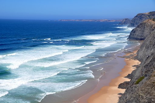 A beautiful beach viewed from a cliff top with sets of waves rolling in