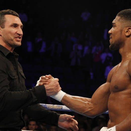 Klitschko and Joshua shake hands in the middle of a boxing ring after the announcement of their fight. Klitschko wears a black shirt, Joshua is dressed for battle with top off and ring shorts