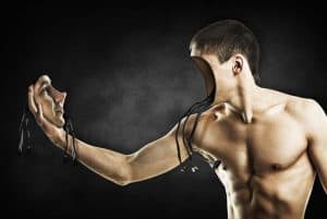 A bare torsoed man holds his face in his hand as it stares at him. Wires hang from inside his head and off the back of his face, it seems he is a robot