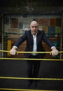 Steve Bunce stands in a boxing ring holding the top of four yellow ropes. He looms over them looking straight into camera