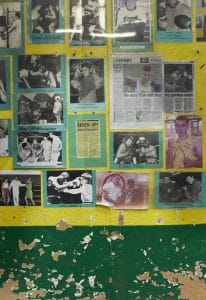 Cut our articles and photos of boxing successes on a tatty green and yellow wall in a boxing gym. Taken during a photoshoot with Steve Bunce