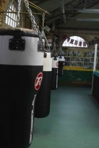 A row of heavy punch bags hang up in a line in a boxing gym in a photo shoot with Steve Bunce