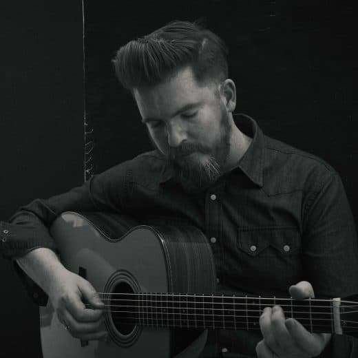 Folk singer and guitarist John Smith stood playing his guitar with his eyes closed. The photograph is black and white and he is wering a dark shirt with white buttons