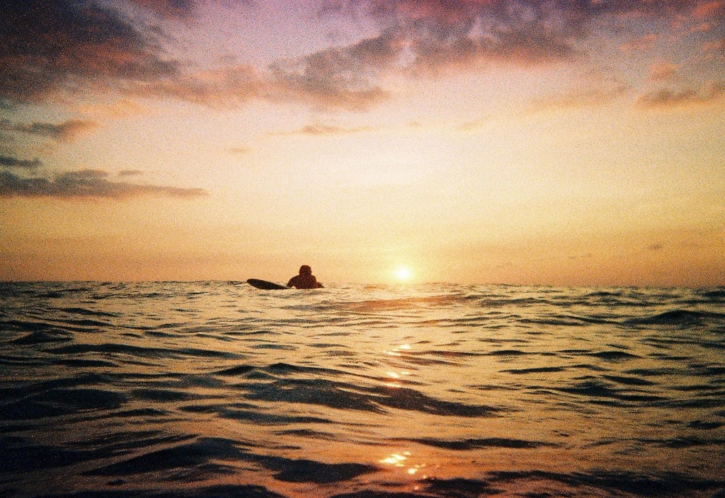 A surfer lies on his board ready to catch a wave as the sun sets below the horizon of the sea behind him