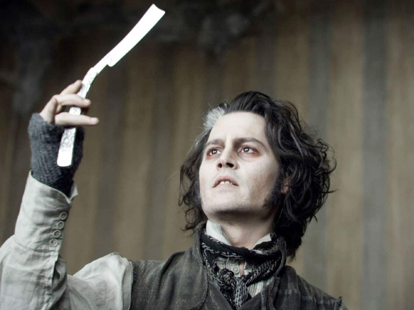 A picture of Johnny Depp in Sweeney Todd © Warner Brothers. He holds out a razor blade in front of his face