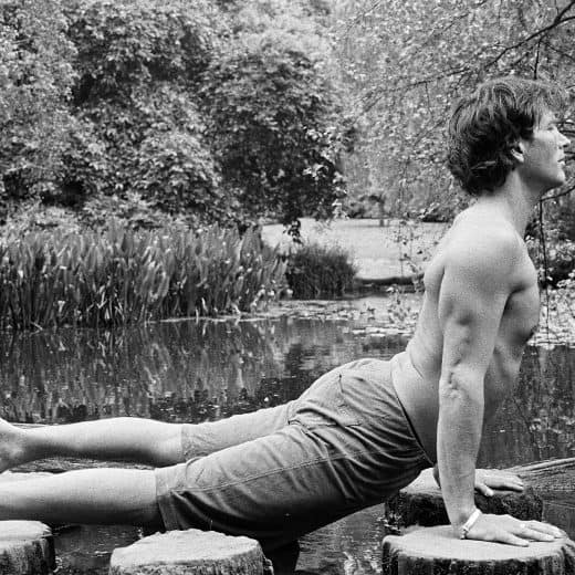 Wellness guru Chris James holds a prone cobra yoga move in a black and white picture. Chris is topless with shorts on. He's side on to camera with a backdrop of trees