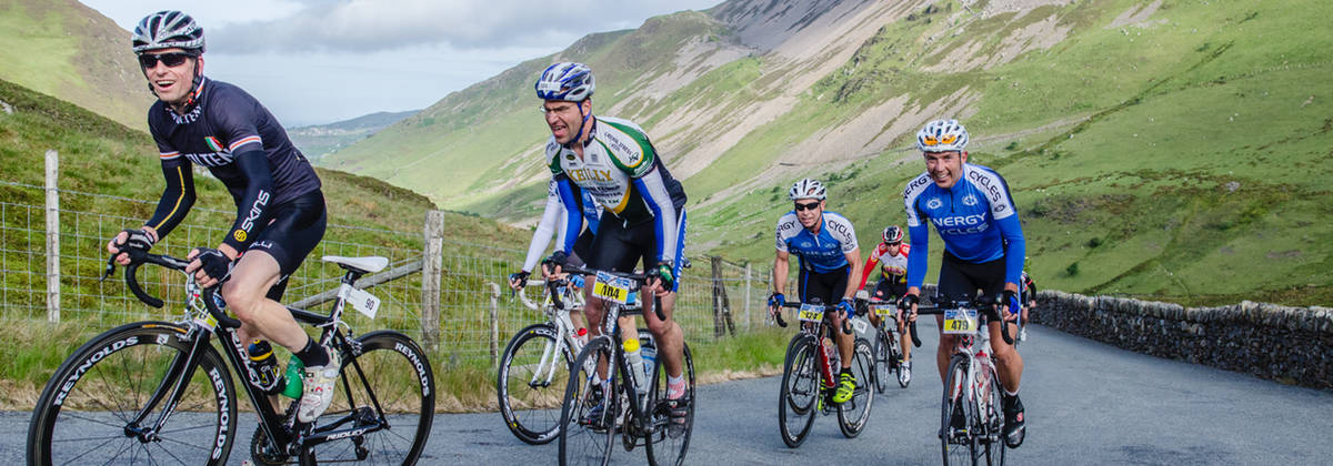 Cyclists pedal their bike uphill during Snowdonia Etape Eyryw