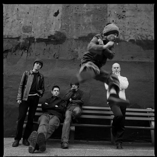 Radiohead stand and sit behind Thom Yorke as he does a flying kick to camera