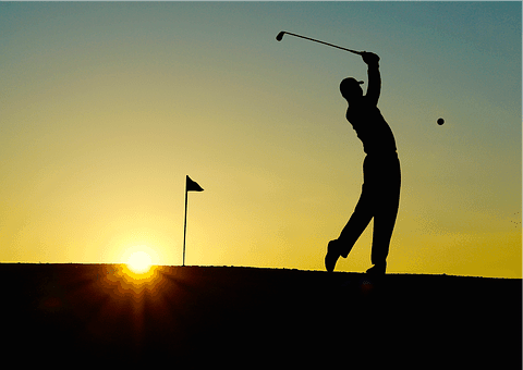 The silhouette of a golfer teeing off as the sun sets in the background