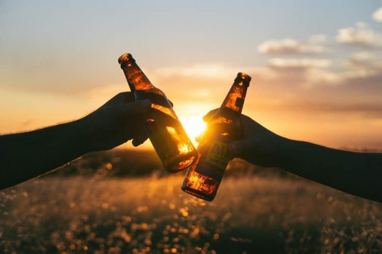 Hands 'Cheers' beer bottles together
