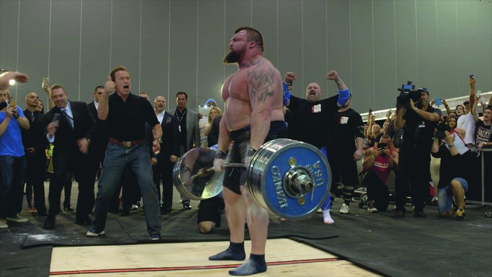 Strongman Eddie Hall deadlifting being cheered on by Arnold Schwarzenegger
