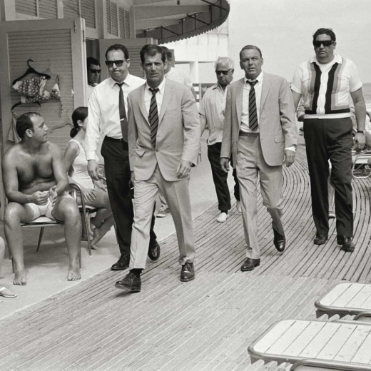 Frank Sinatra walking with his minders