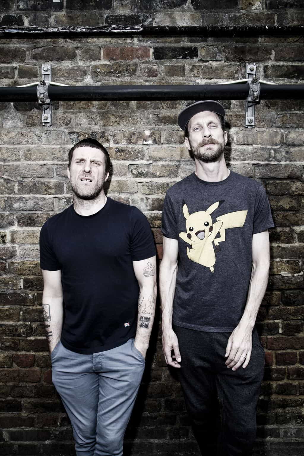 Sleaford Mods stood against a wall