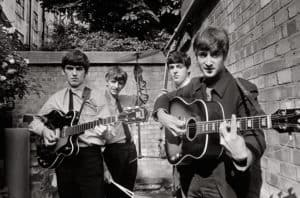 The Beatles posing with their instruments
