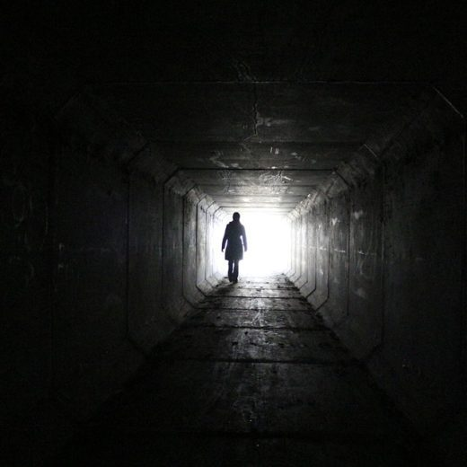 The silhouette of a man in a dark tunnel walking towards the light