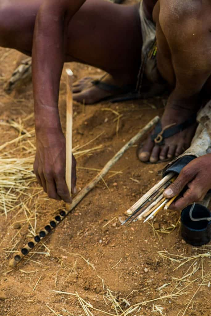 A tribesman using a bow drill