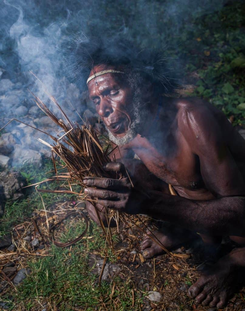 A tribesman blows a tinder