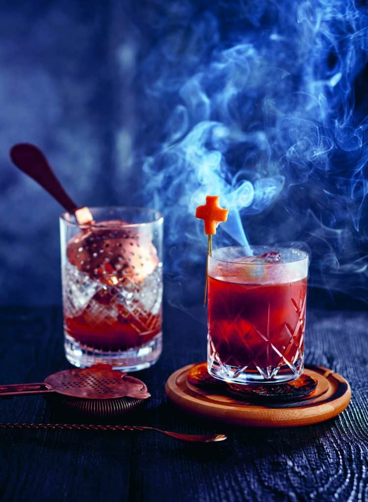 A glass of coffee and cigarettes on a wooden table in a smoke filled atmosphere