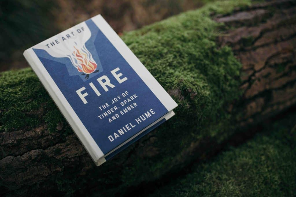A copy of The Art of Fire sat on a log