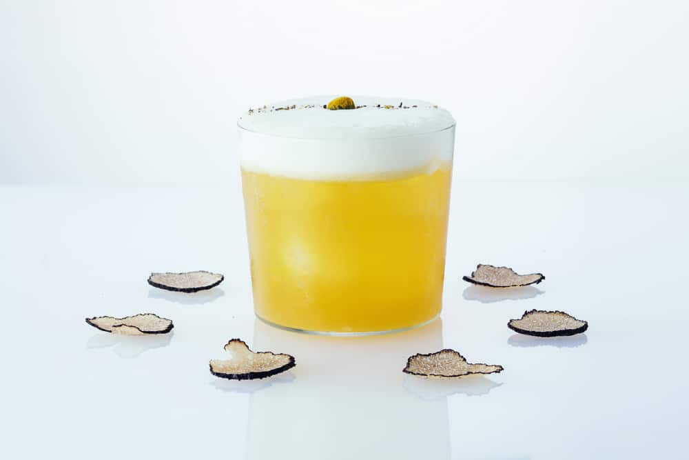 A glass of field notes encircled by slices of truffle