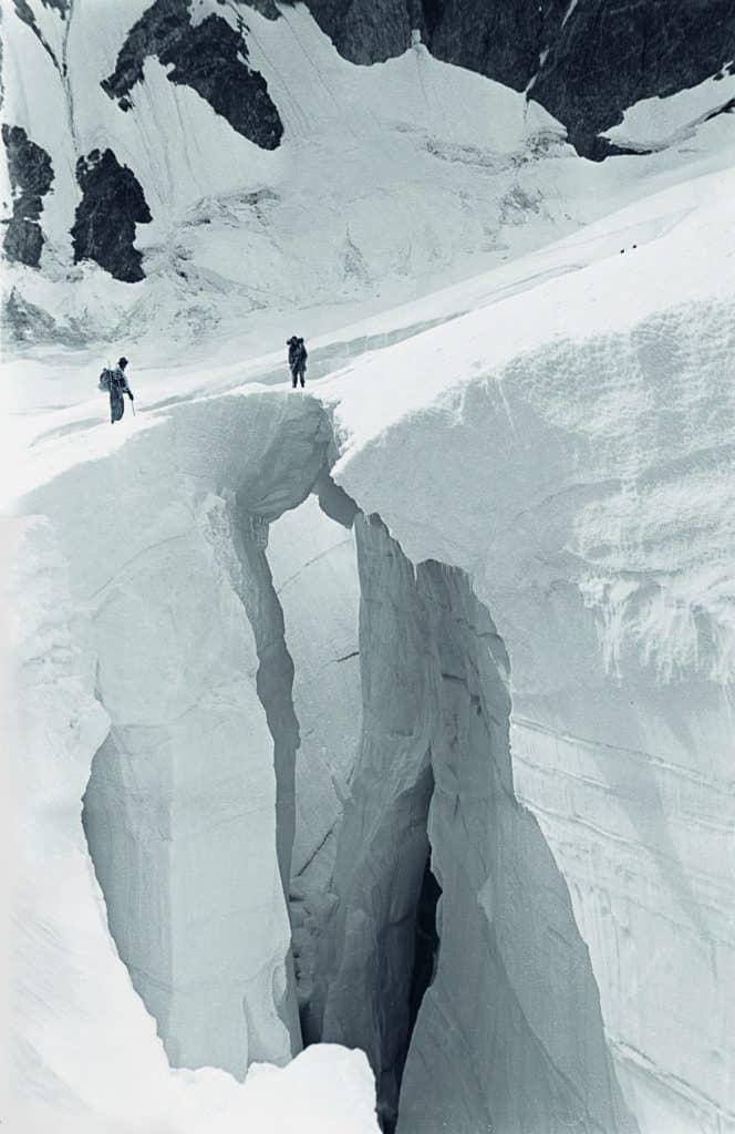 Crossing a crevasse on the Tiedemann Glacier beneath Mount Waddington.