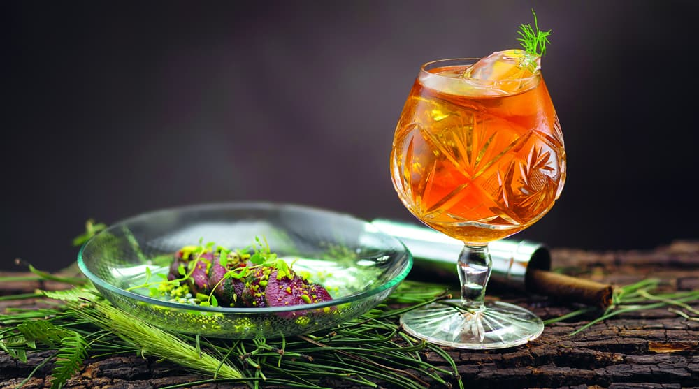 A glad of Deer Hunter on a wooden block garnished with herbs