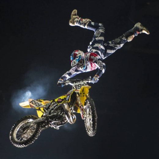Travis Pastrana upside down holding onto a motorbike