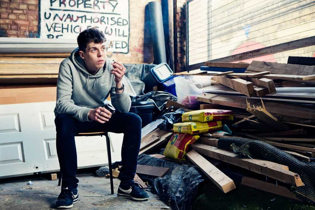 Comedian Ed Night sits on a chair looking into distance holding a coffee and a cigarette