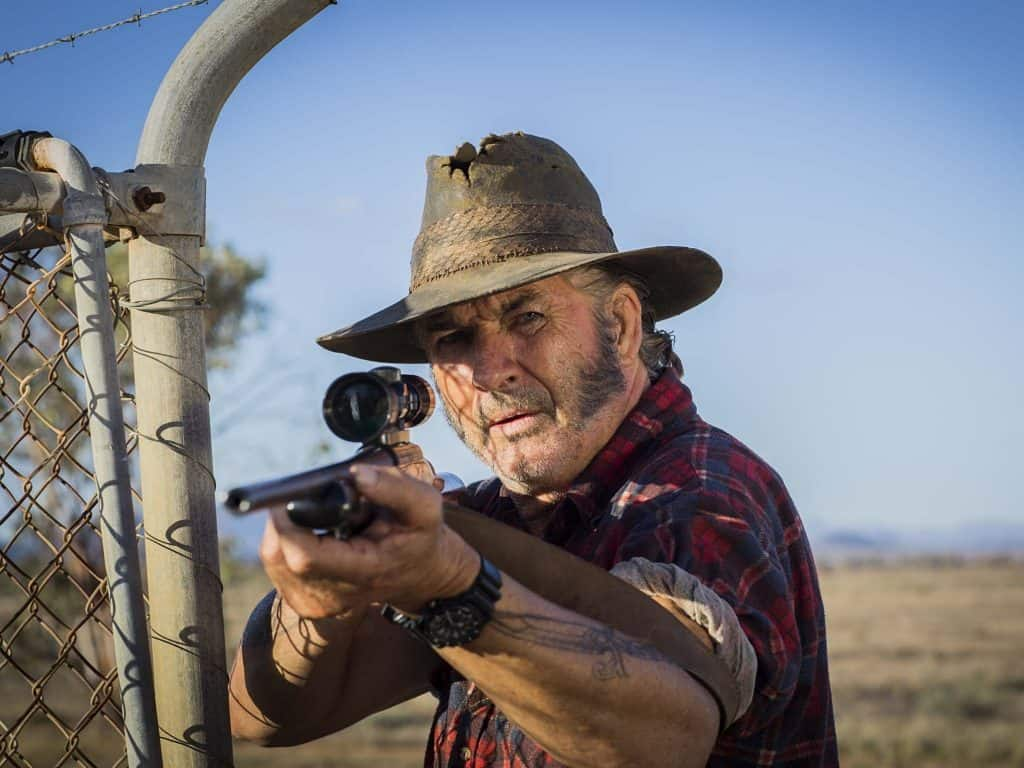 Mick Taylor points a rifle at his target