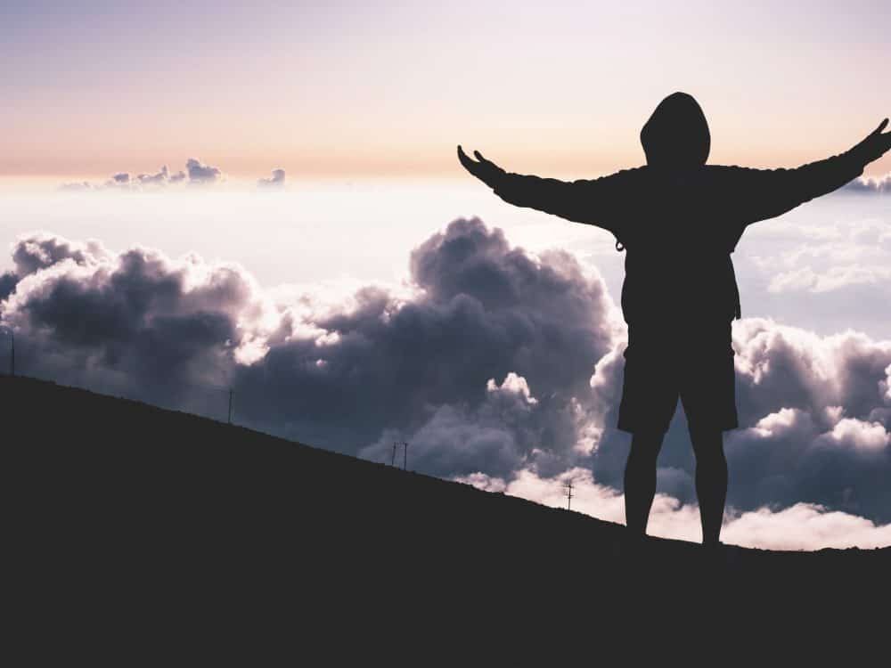 A man at the top of a mountain looking at the clouds