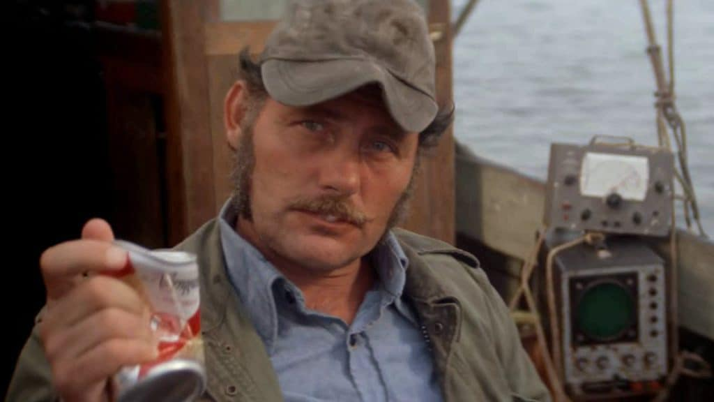 Quint crushes a beer can in his hands as he sits on the boat
