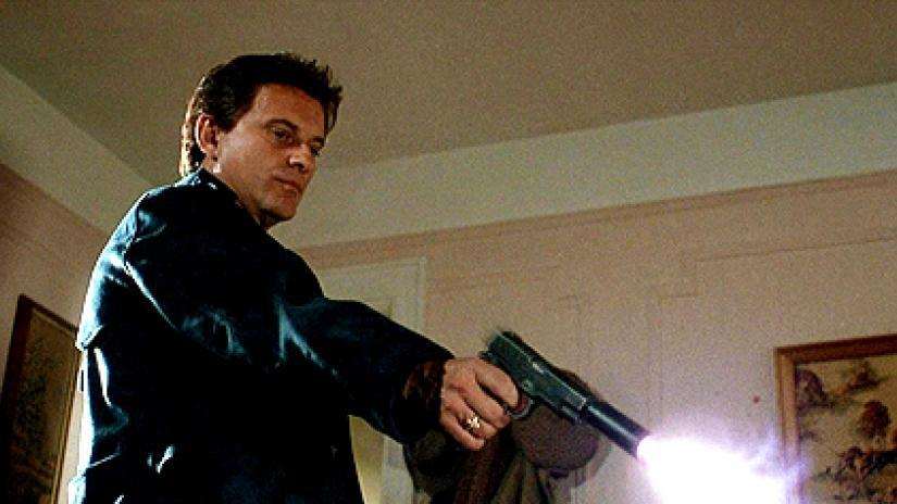 Tommy DeVito firing a shot downwards with his pistol