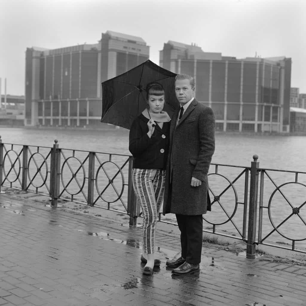 Two mods posing under an umbrella next to the river Thames