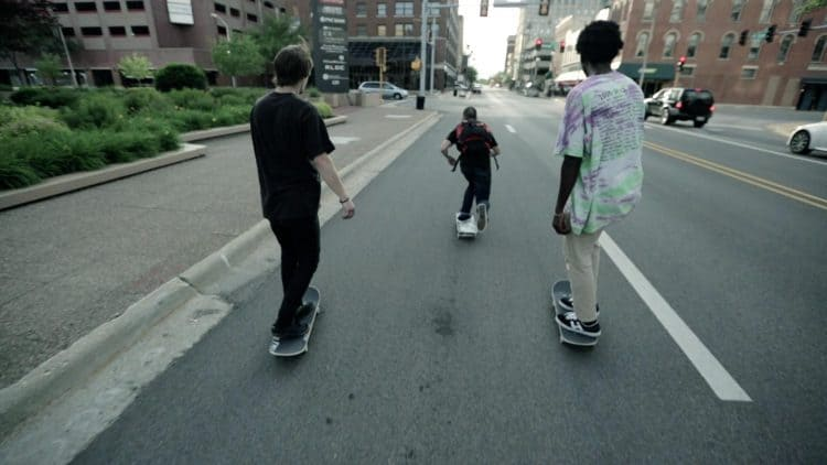 Three young men skateboarding down a road