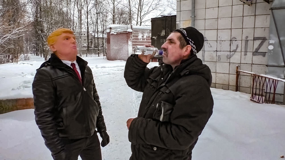A man drinks from a bottle stood with a man in a Donald Trump mask