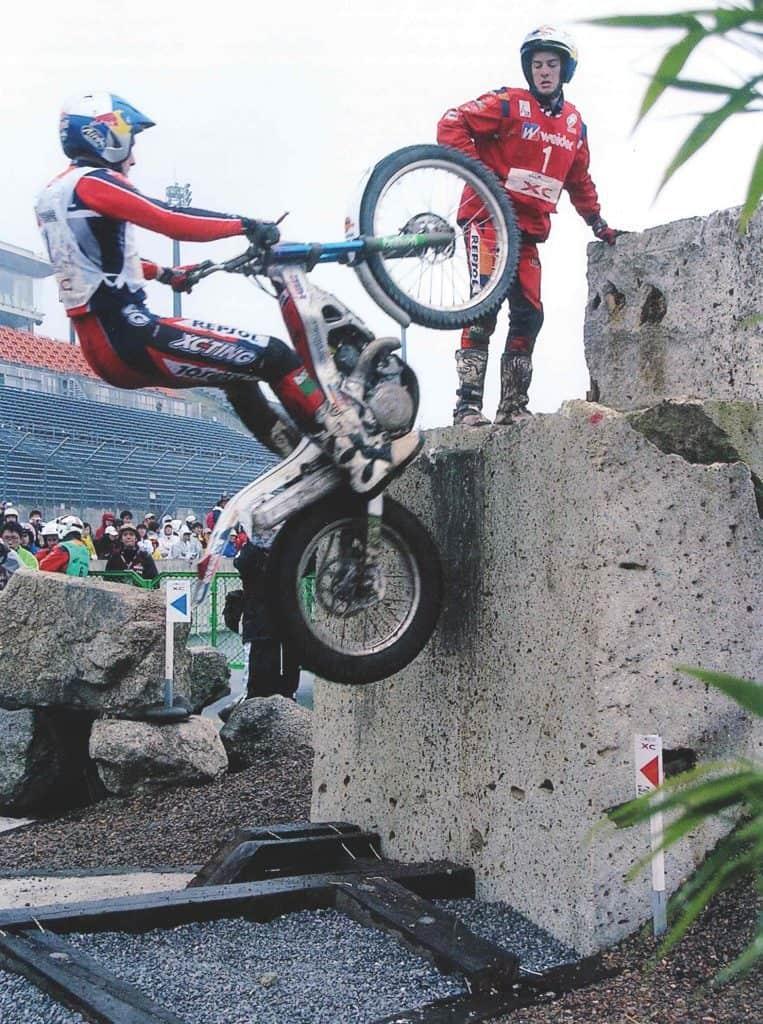 Trial biker Dougie Lampkin riding up a vertical concrete wall