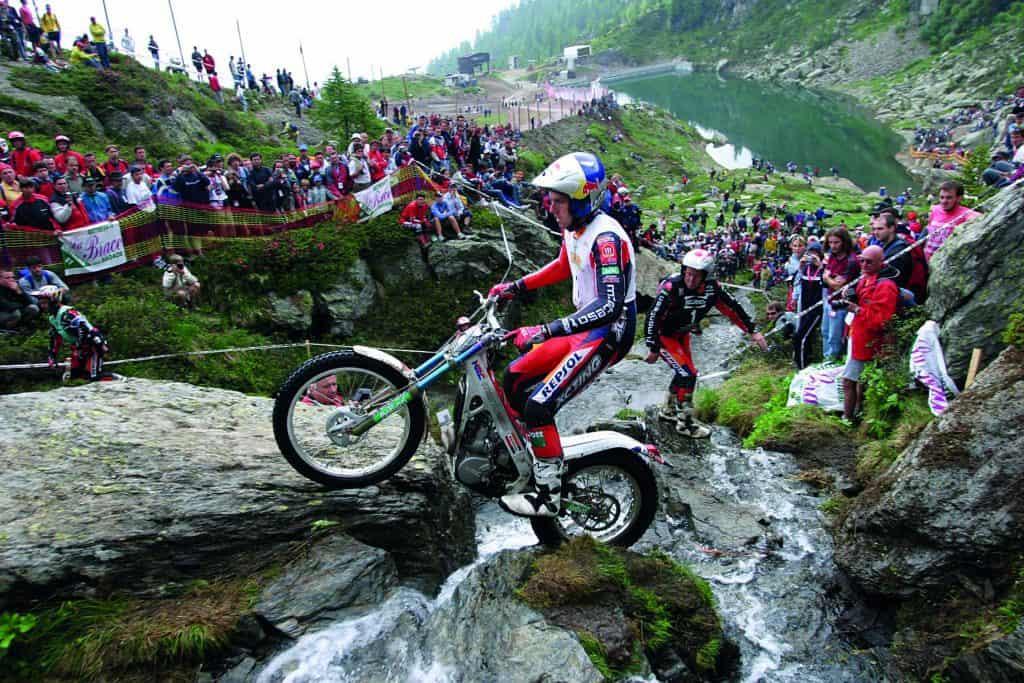 Trial biker Dougie Lampkin riding up rocks