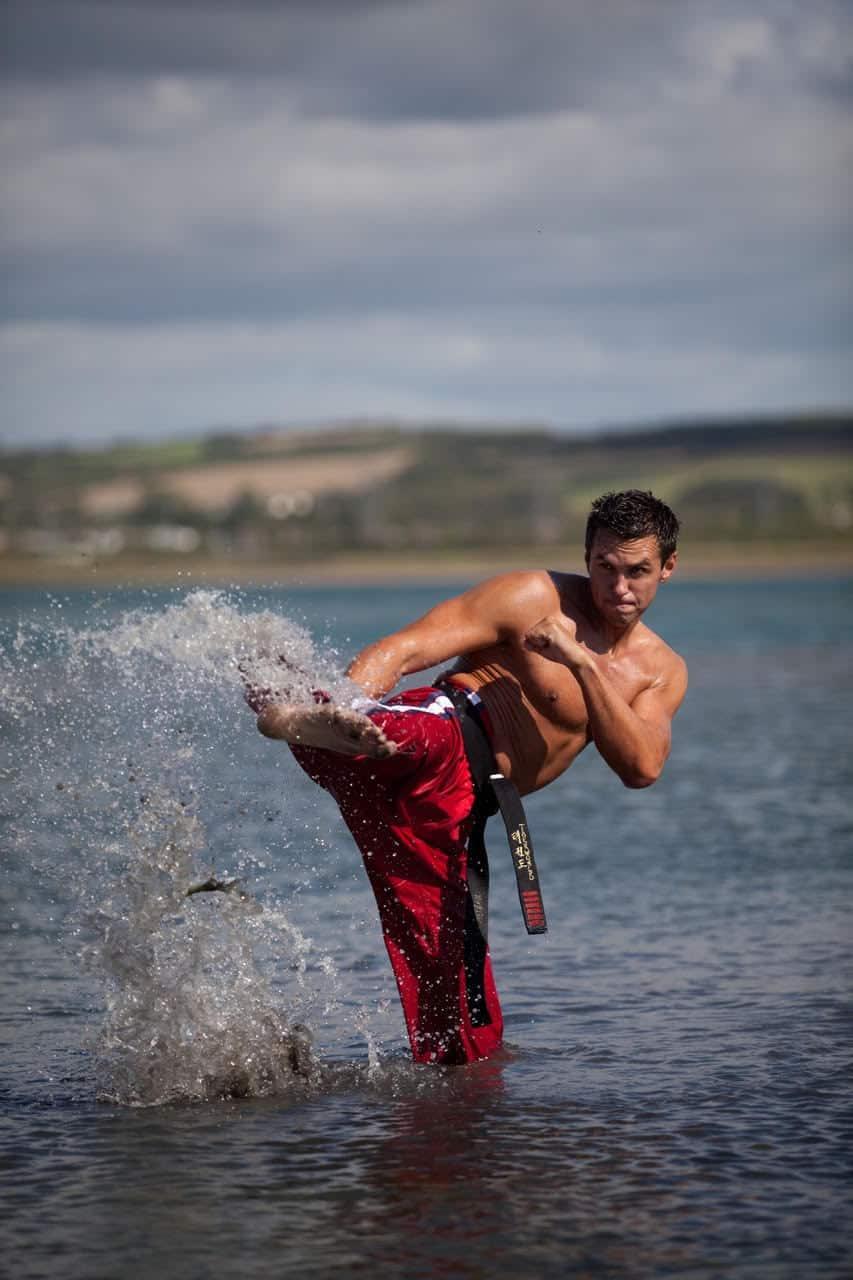 Matt Fiddes performs a karate kick in the sea