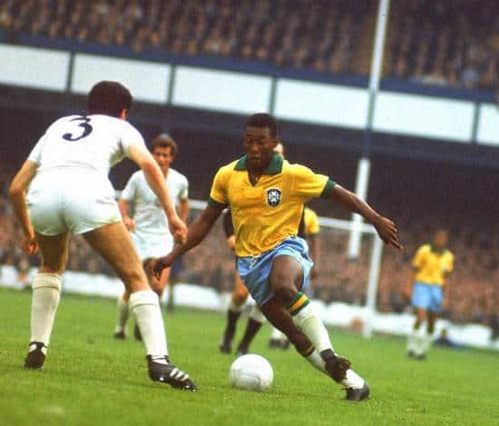 Pele dribbles the ball in the Brazil 1970 kit